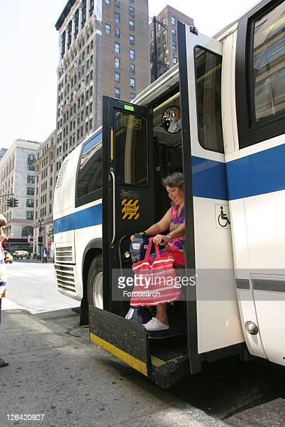 Woman with a disability (carrying a bright pink striped tote!) exiting a city bus via a lift.