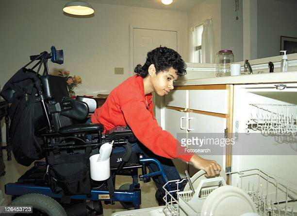 woman with a disability, utilizing a wheelchair for mobility, unloading her dishwasher in her apartment. - cerebrum stock pictures, royalty-free photos & images