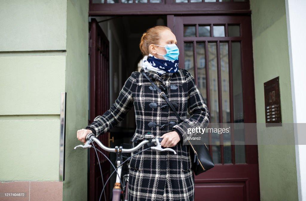 Femme avec un masque de visage sortant avec son vélo : Photo