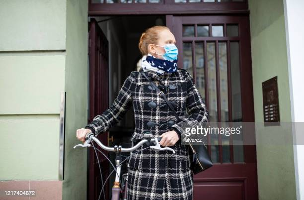 femme avec un masque de visage sortant avec son vélo - leaving photos et images de collection