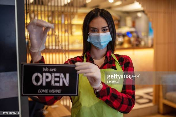 """woman with a face mask holding an """"open"""" sign in her hands - reopening stock pictures, royalty-free photos & images"""