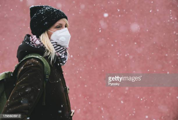 woman with a face mask in a snowfall - fingerless gloves stock pictures, royalty-free photos & images
