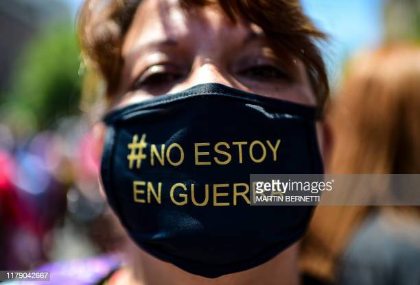 """Woman with a face mask reading """"#IAmNotAtWar demonstrates against the government economic policies in front of La Moneda presidential palace in..."""