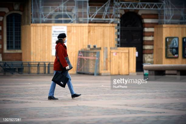 A woman with a face mask walks on Capitole square as France is on lockdown On Monday March 16th French President Macron announced that all people...