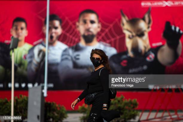 Woman with a face mask walks outside the Caliente Stadium prior the 8th round match between Tijuana and Monterrey as part of the Torneo Guard1anes...