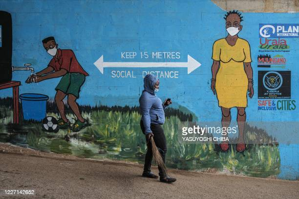 Woman with a face mask walks past graffiti that promotes social distancing, to curb the spread of the COVID-19 coronavirus, in Kibera, Nairobi, on...