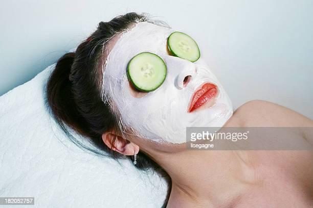 Frau mit einer Gesichtsmaske und Gurke Augen