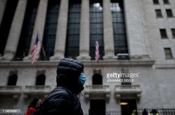 A woman with a facial mask passes the New York Stock Exchange on February 3 2020 at Wall Street in New York City Wall Street stocks rose early Monday...
