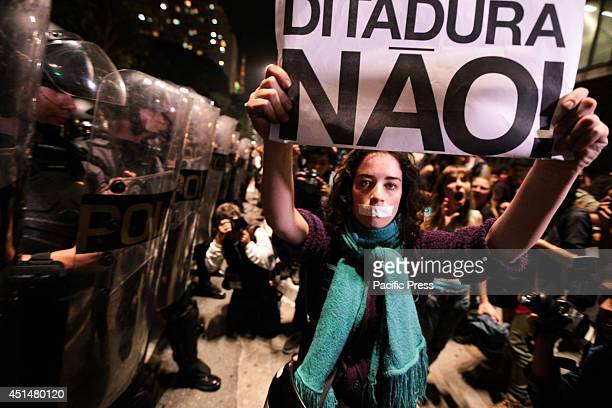 A woman with a gag in her mouth holds a sign that says 'No to dictatorship' during their protests against the arrest of two people from a...