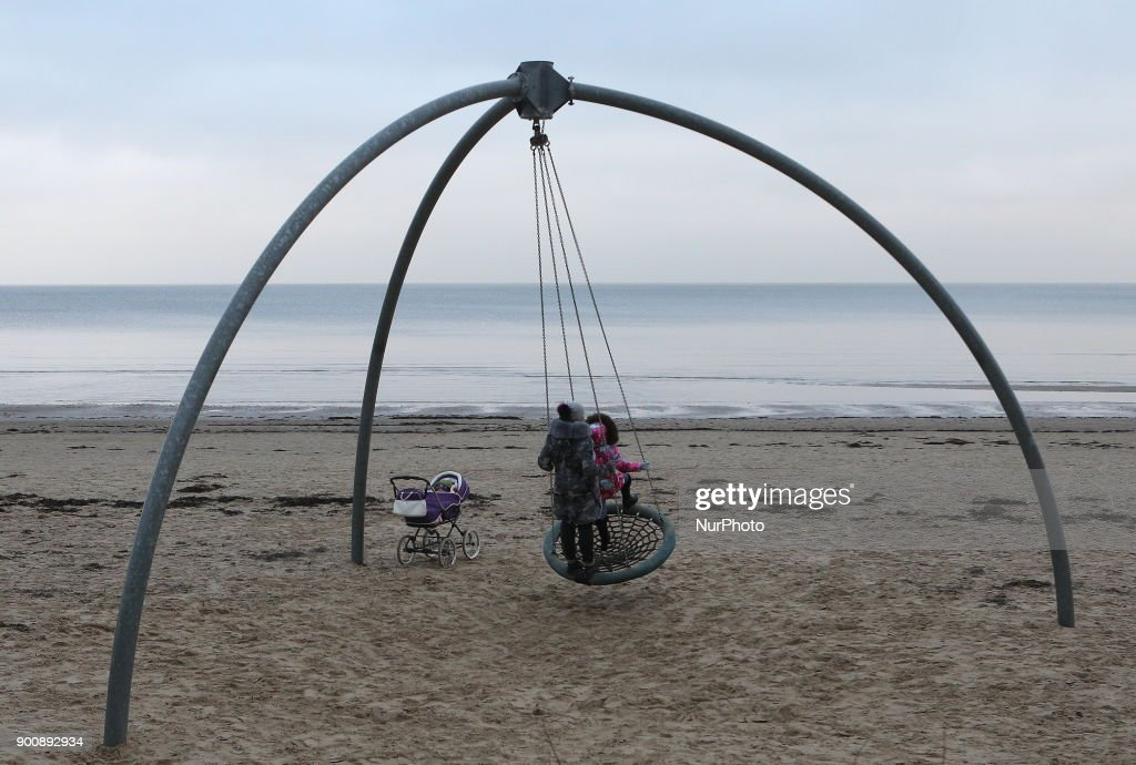 A woman with a girl is riding a swing on the embankment of the Gulf of Riga in Jurmala, 25 km from Riga. Latvia, Wednesday, January 3, 2018 The resort is famous for wooden Art Nouveau villas, Soviet-era sanatoriums and a long sandy beach.