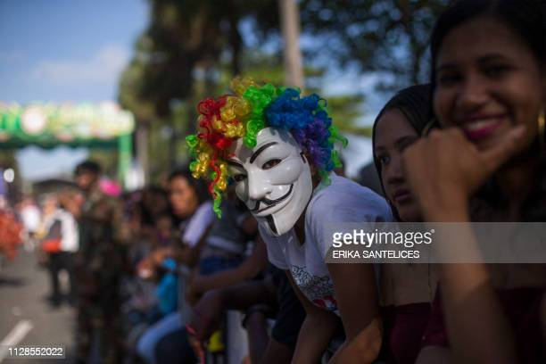 TOPSHOT A woman with a Guy Fawkes mask looks at a parade along the Malecon avenue in Santo Domingo during carnival celebrations on March 3 2019