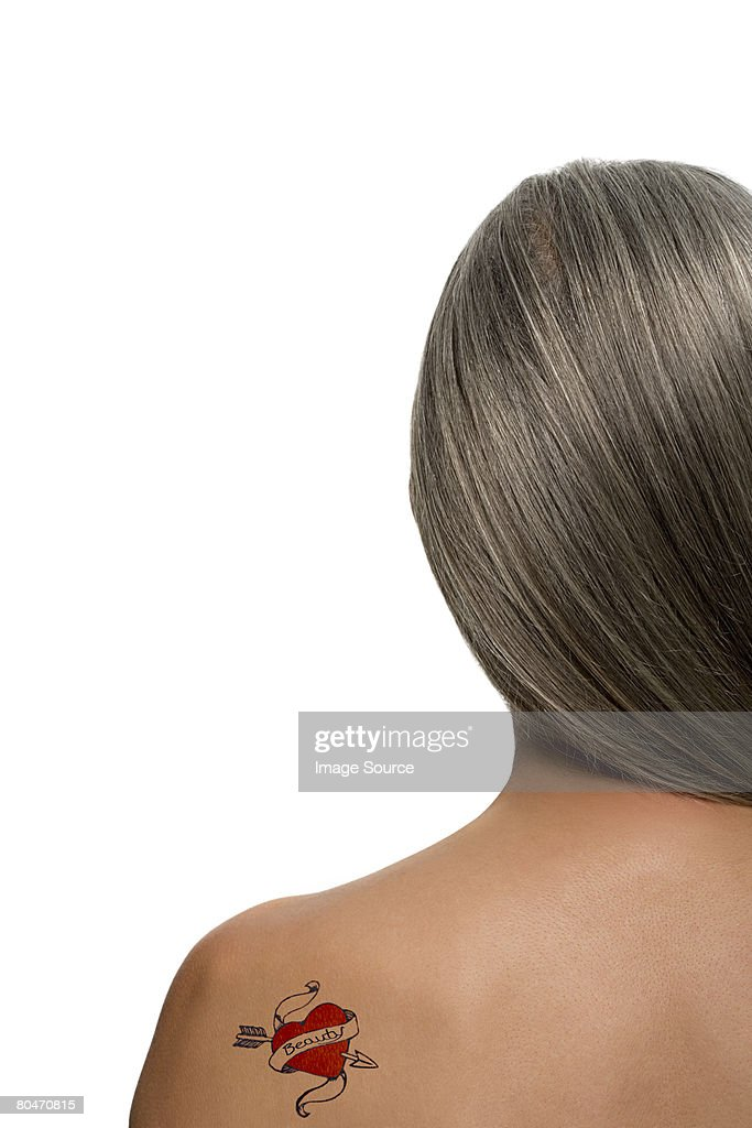 Woman with a heart shaped tattoo on her back : Stock Photo