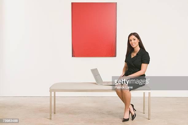 woman with a laptop computer in an art gallery - kunsthändler stock-fotos und bilder