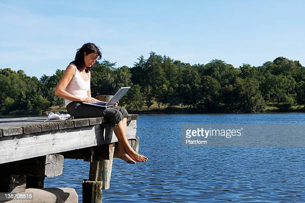 A woman with a laptop on a jetty by a lake, Sweden.