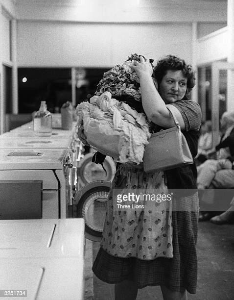 A woman with a large load of laundry in a New York laundromat