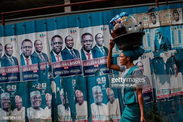 TOPSHOT A woman with a large plastic bucket filled with drinks and food on her head passes by a wall covered with posters of presidential candidate...