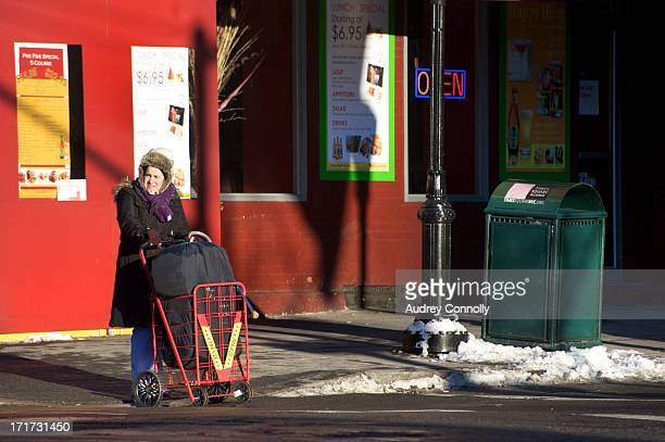 CONTENT] woman with a laundry basket on street corner in Hell's Kitchen Manhattan New York City