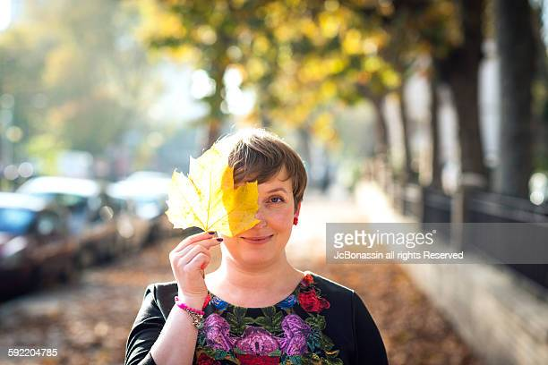 woman with a leave in her face autumn - jcbonassin stock pictures, royalty-free photos & images