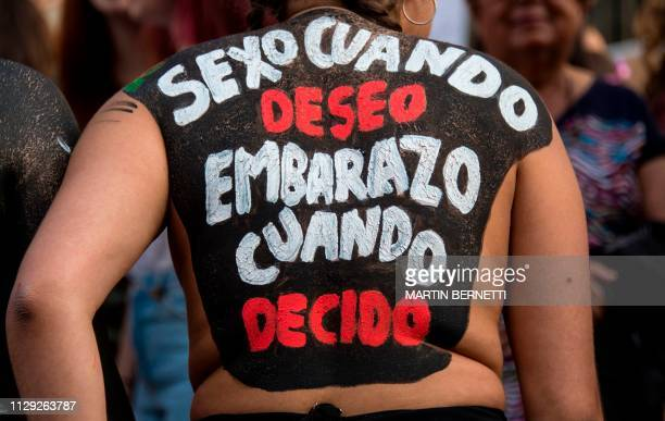 A woman with a legend written on her back reading 'Sex when I want pregnancy when I decide' takes part in a march on the International Women's Day in...