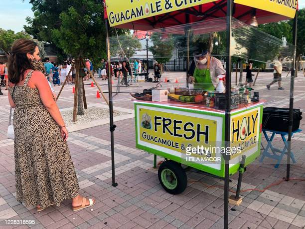 A woman with a leopard dress and a matching mask waits in front of a guacamole and chips stand wrapped in plastic due to covid19 concerns in Key West...