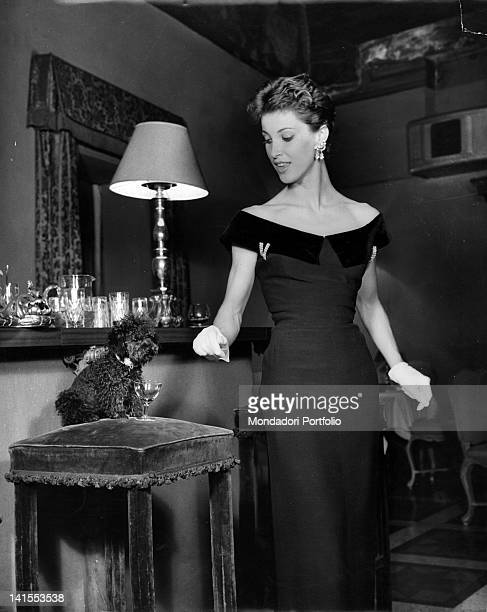 A woman with a lowcut dress and gloves looking at a poodle dog 1955