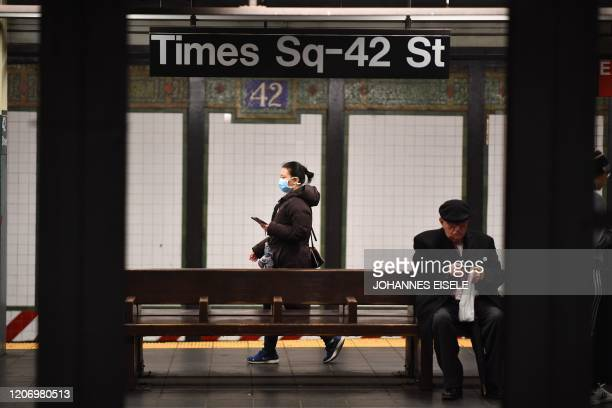 A woman with a mask waits for a subway at the Plattform at Times Square on March 13 2020 in New York City The World Health Organization said March 13...