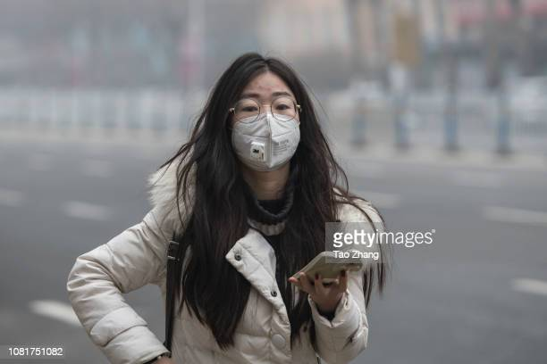 A woman with a mask walks amid heavy air pollution on January 13 2019 in Harbin China Meteorological authorities have issued an orange alert for...