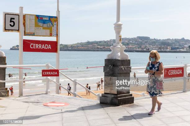 Woman with a mask walks in front of a closed access to the San Lorenzo beach, Gijon, Asturias, Spain, on July 14 with limited capacity due to the...