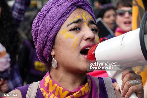 A woman with a megaphone shouts slogans during a march on the International Women's Day in Quito on March 08 2019 Protests strikes and studies people...