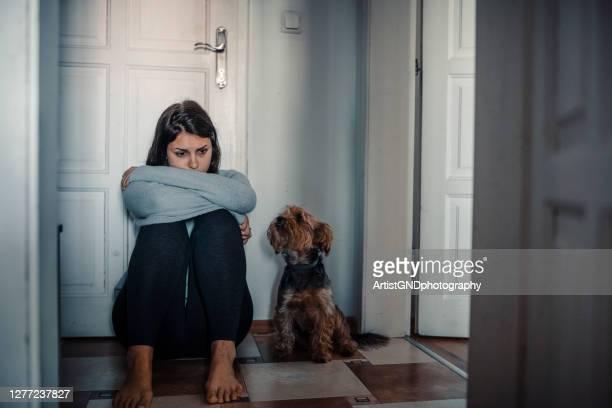 donna con problemi mentali è seduta esausta sul pavimento con il suo cane accanto a lei - suicidio foto e immagini stock
