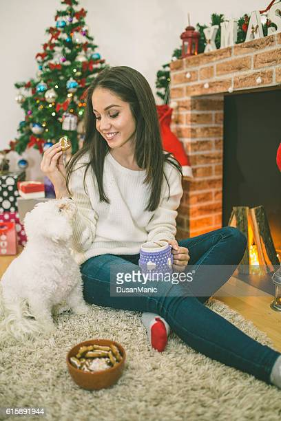 Woman with a mug by the fireplace.