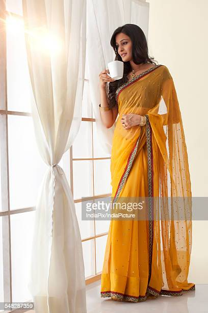 Woman with a mug of tea looking out a window