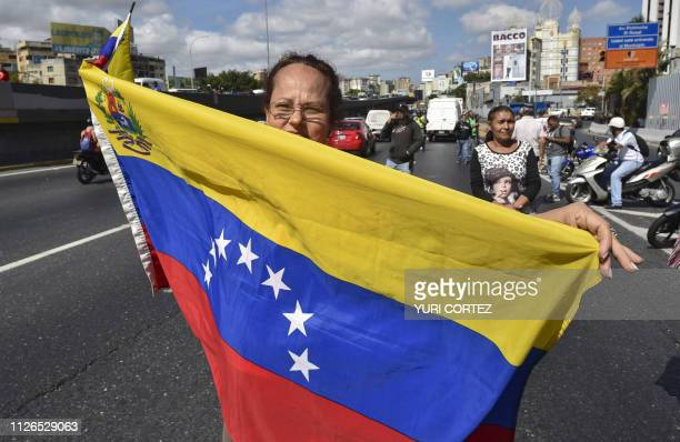 A woman with a national flag waits on the side of a highway in Caracas to see a caravan of buses organized by opposition leader and selfdeclared...