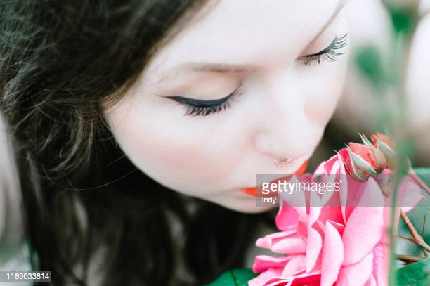 woman with a nose ring smelling roses - sensory perception stock pictures, royalty-free photos & images