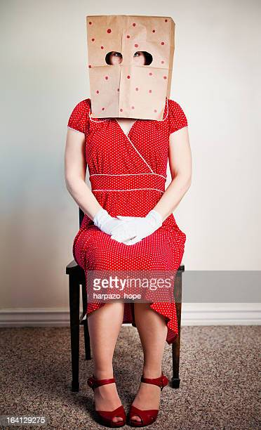 A woman with a paper bag over her head.