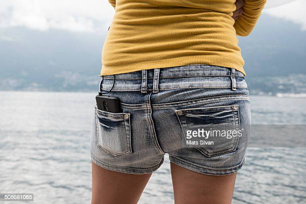 Woman with a phablet in her jeans shorts back pocket
