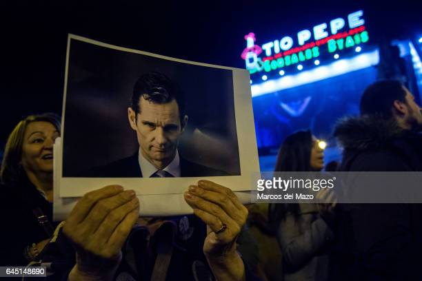 A woman with a picture of I Urdangarin protesting against corruption case Noos I Urdangarin has been sentenced with jail for six years and three...