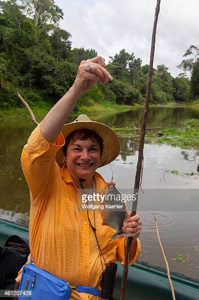 A woman with a Piranha on a small river in the PacayaSamiria National Reserve along the Ucayali River in the Peruvian Amazon River basin near Iquitos