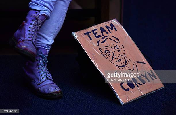 TOPSHOT A woman with a placard in support of Britain's opposition Labour party leader Jeremy Corbyn listens to hims speak at a rally for the National...