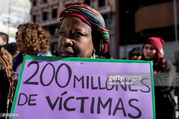 A woman with a placard that reads 200 million victims protesting against female genital mutilation