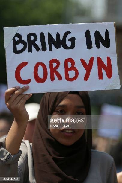 A woman with a placard that reads 'Bring in Corbyn' marches with other demonstrators through London on June 21 2017 en route to Parliament during an...