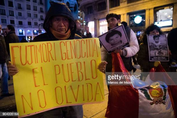 """Woman with a placard that reads """"Fujimori genocide... People do not forget"""" during a protest against the pardon to Peruvian President Alberto..."""