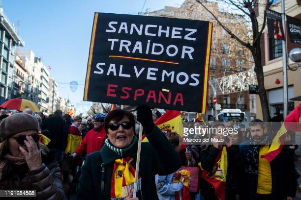 Woman with a placard that reads 'Sanchez traitor. Save Spain' protesting against socialist leader Pedro Sanchez as the first day of the investiture...