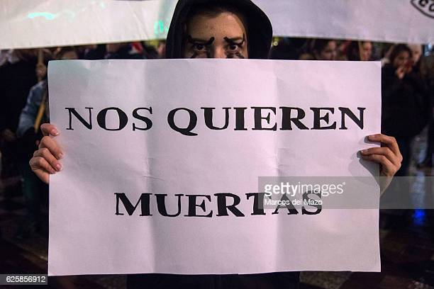 A woman with a placard that reads They want us death protesting against genderbased violence during the International Day for the Elimination of...