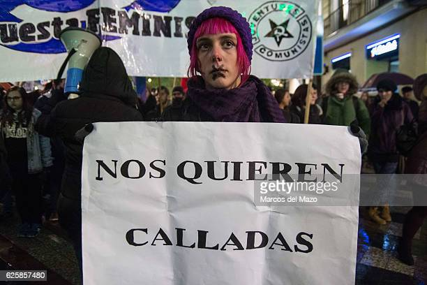 A woman with a placard that reads They want us silent protesting against genderbased violence during the International Day for the Elimination of...