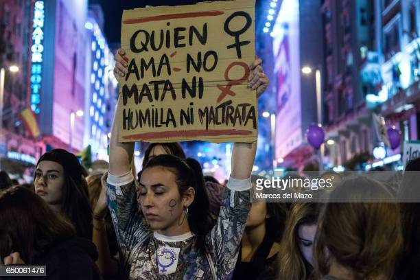 A woman with a placard that reads 'Who loves does not kill or humiliate or mistreat' protesting during a demonstration for International Woman's Day