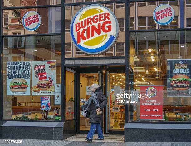 Woman with a plastic face visor leaves Burger King.