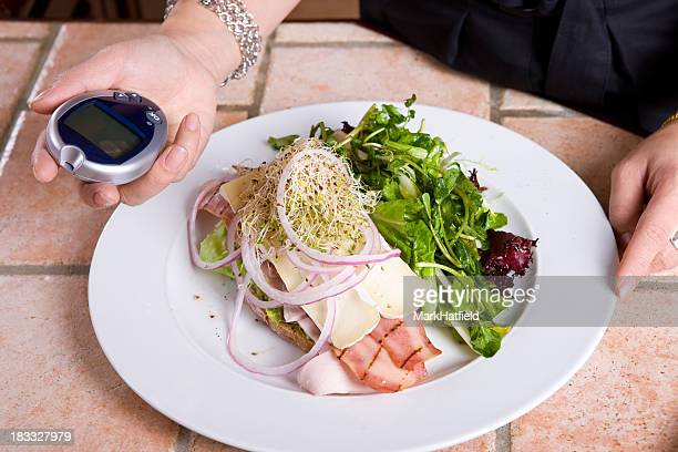 Woman with a plate of food checks her blood sugar in kitchen