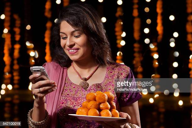 woman with a plate of sweets reading an sms - mithai stock pictures, royalty-free photos & images