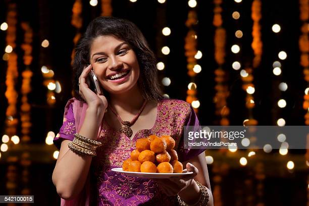 woman with a plate of sweets talking on mobile phone - mithai stock pictures, royalty-free photos & images